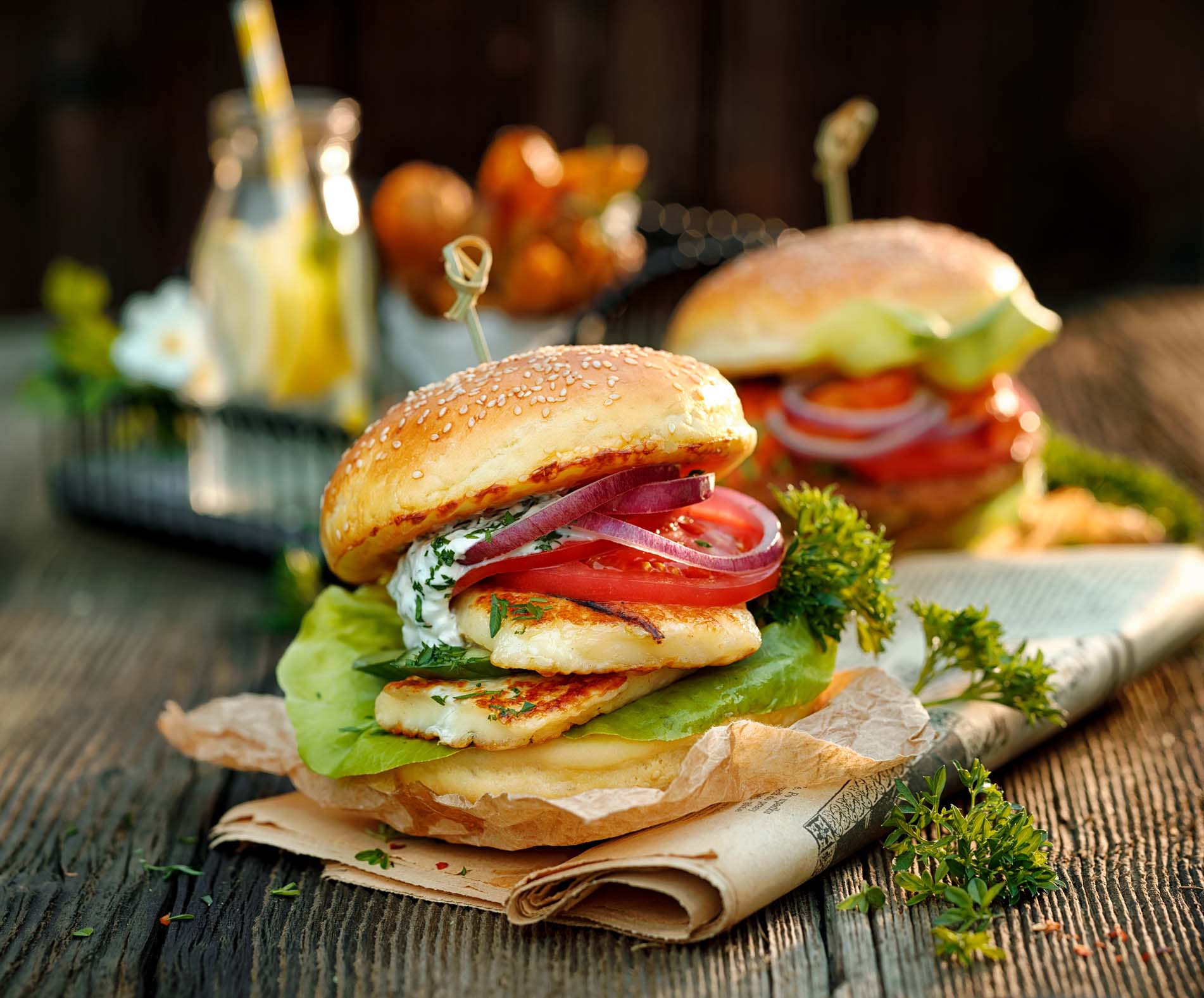 A pair of hamburgers with onions, tomatoes and halloumi.