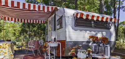 A vintage trailer festooned in autumn-Halloween decor.