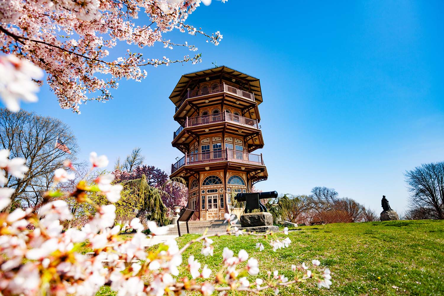 A pagoda structure towers over cherry blossoms in the foreground.