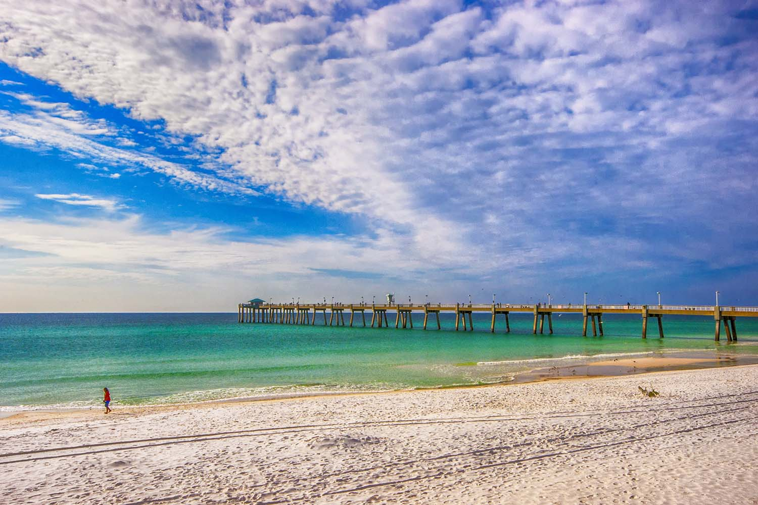 A pier stretches into emerald waters from a white-sand beach.