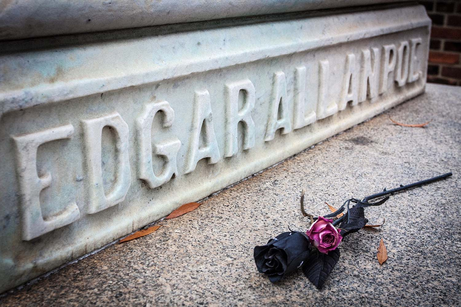 """A gravesite with the raised letters, """"Edgar Allan Poe"""" and rose."""