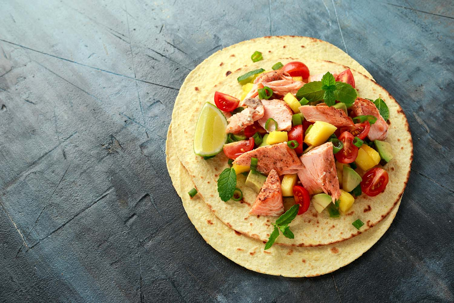 Kid-friendly recipes —Salmon fish tacos with mango, avocado, tomato, spring onion and lime. Mexican food