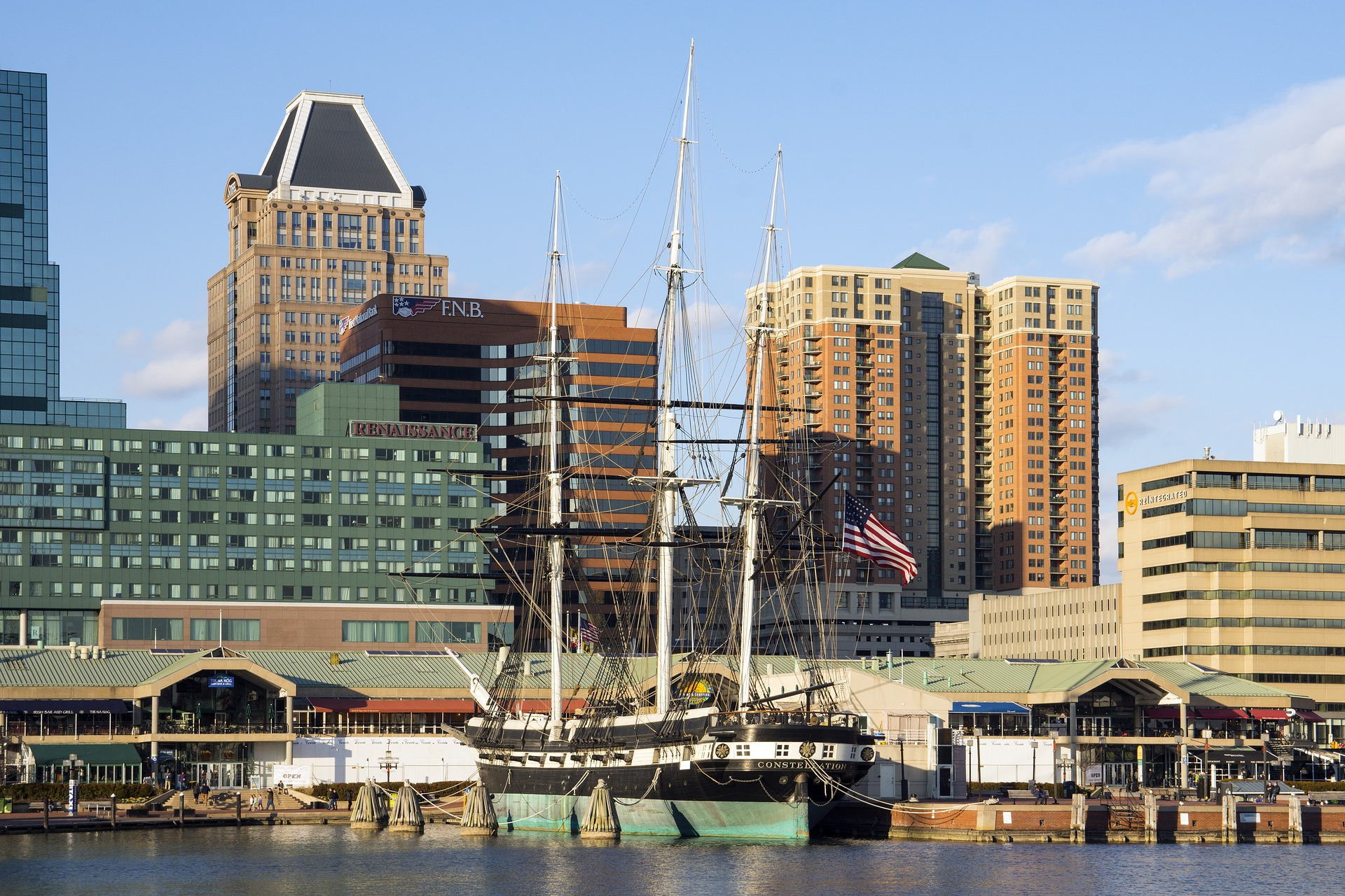 A tall ship moored to a dock with tall buildings in the background.